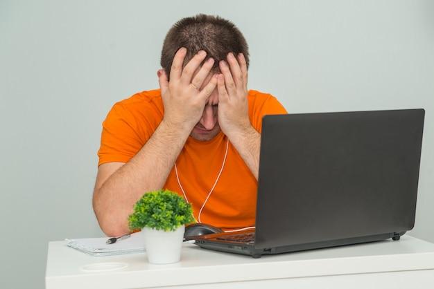 オレンジ色のシャツで疲れた過労男は、ラップトップの近くに座って頭を抱えています。オンライン作業。オンライン教育のコンセプト