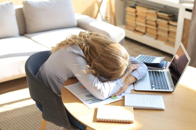 피곤한 과로한 여성이 노트북 작업을 하는 동안 쉬고 있습니다.