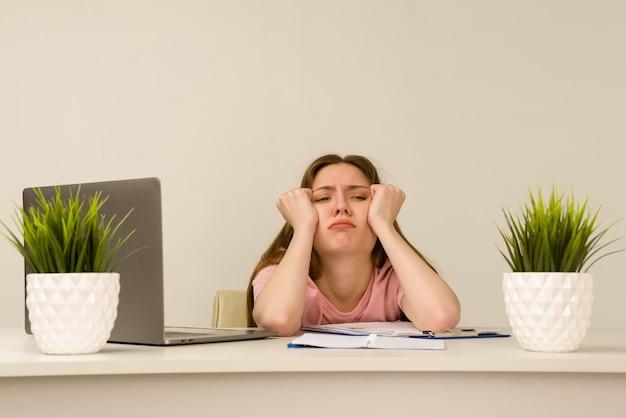 Усталая переутомленная молодая женщина-интерн, работающая с ноутбуком в офисе
