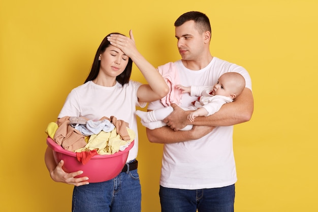Усталые родители пытаются сгладить плач новорожденного, мама держит в руках таз с одеждой и держит ладонь на лбу, папа с новорожденной девочкой, много домашней работы, изолирован на желтой стене.