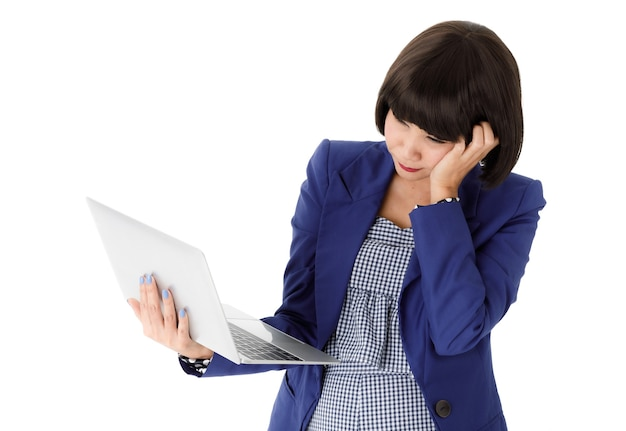 Tired pensive young asian female in stylish outfit leaning on hand and looking at laptop screen while working online against white background