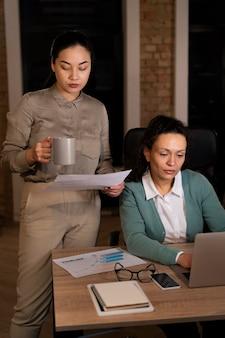 Persone stanche in ufficio che lavorano fino a tardi