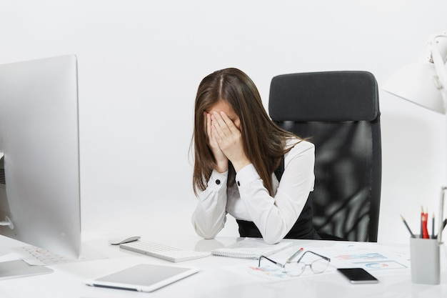 Tired perplexed and stress brown-hair business woman in suit sitting at the desk, covering her face with hands, working at contemporary computer with documents in light office