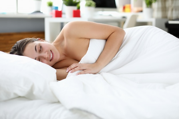 Усталый человек под белым пуховым одеялом