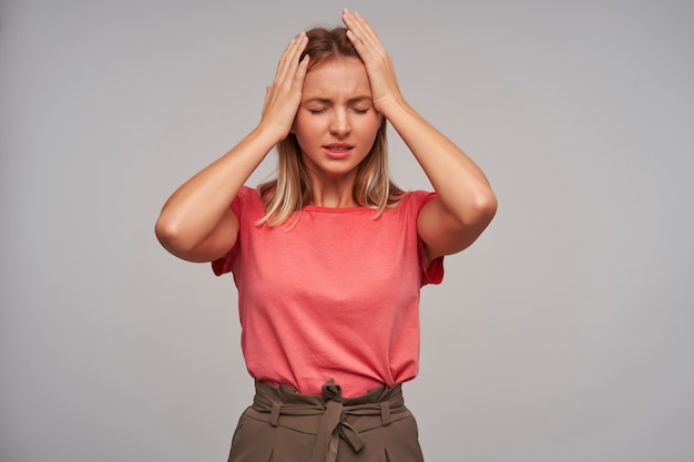 Tired pleasant looking young blonde lady with casual hairstyle closing eyes and frowning eyebrows because of strong headache, wearing casual clothes over white background