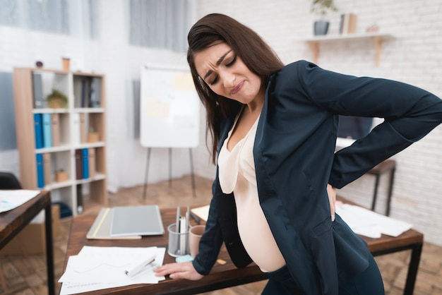 Tired pregnant woman having backache at work