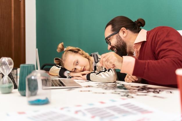 Усталая довольно светловолосая девушка с браслетами на руке чувствует усталость, думая о буквах