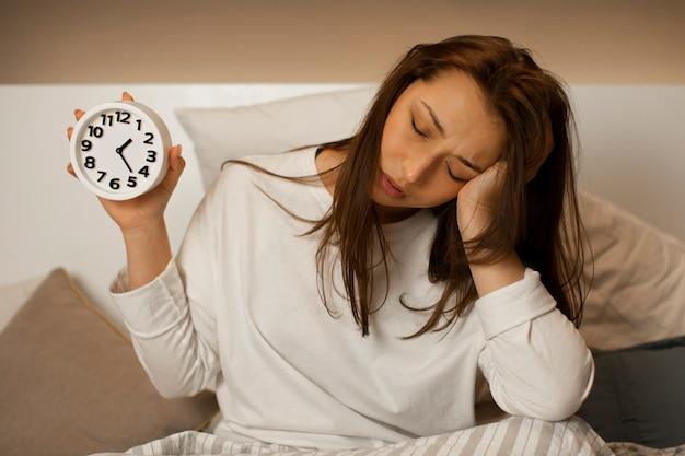 Усталая красивая девушка, вздремнуть, сидя в постели с будильником в руке
