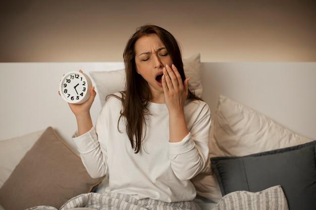 Утомленная милая девушка зевает сидя в кровати с будильником в руке