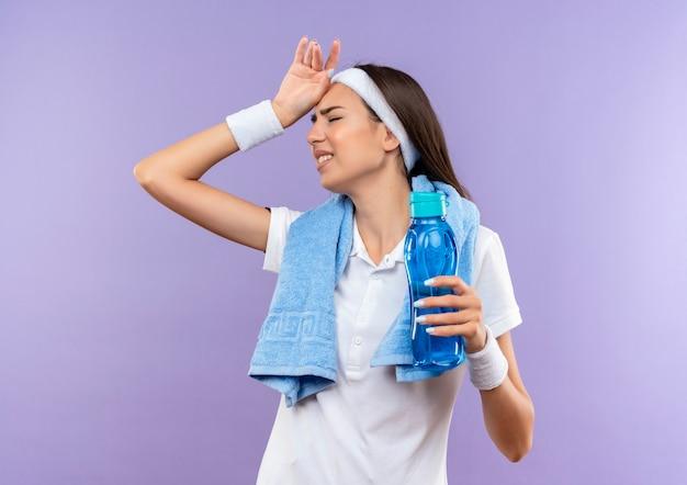 Усталая симпатичная спортивная девушка с повязкой на голову и браслетом держит бутылку с водой, положив руку на голову с закрытыми глазами и полотенцем вокруг шеи, изолированным на фиолетовом пространстве