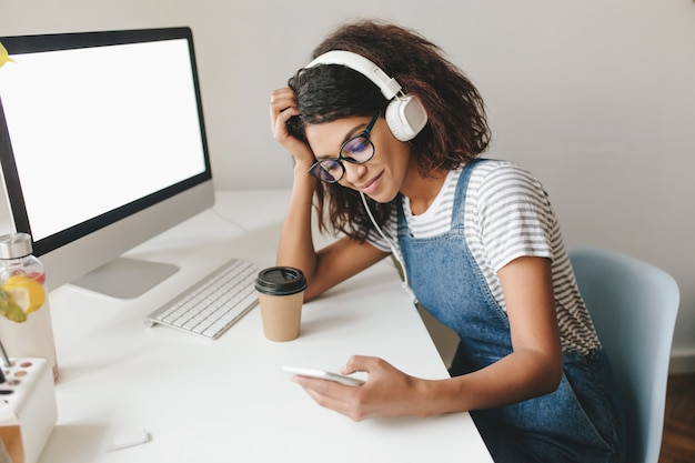 Stanco piuttosto giovane donna seduta al posto di lavoro appoggiando la testa e il messaggio di testo, tenendo il telefono