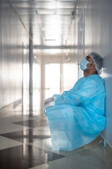 Усталый профессиональный хирург-мужчина в защитной спецодежде, прислонившись к стене в коридоре у двери операционной перед следующей операцией