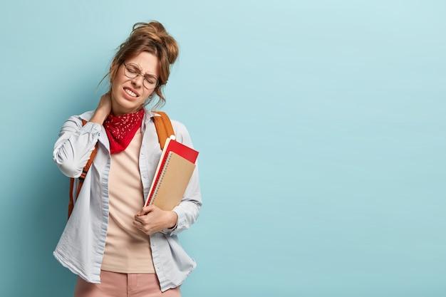 피곤한 학생 또는 학생이 머리를 오른쪽으로 기울이고, 목에 닿으며, 열심히 일한 후 통증을 겪고,이를 움켜 쥔다