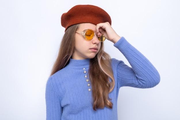 額に手を置くのに疲れた帽子と眼鏡をかけている美しい少女