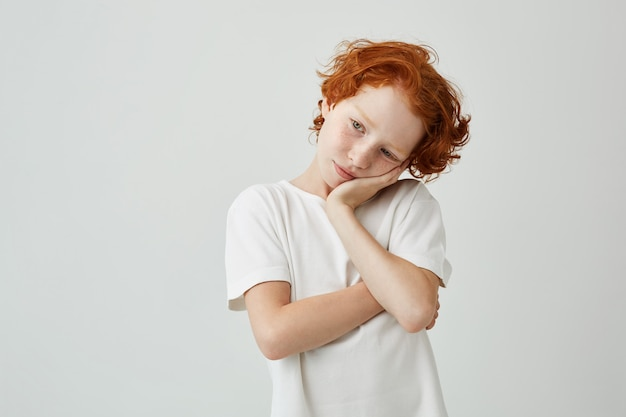 Tired red haired boy with freckles in white t-shirt looking aside with relaxed expression, holding head with hand.