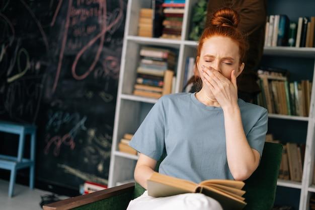 Усталый рыжий студентка читает книгу и наслаждается отдыхом в домашнем офисе