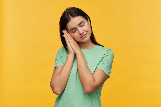 Tired relaxed young woman with dark hair with closed eyes in mint tshirt standing and pretending sleeping on hands isolated over yellow wall