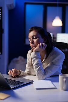 피곤한 원격 여성이 노트북 작업을 하는 의자에서 낮잠을 자며 회사 사무실의 재무 통계를 분석합니다.