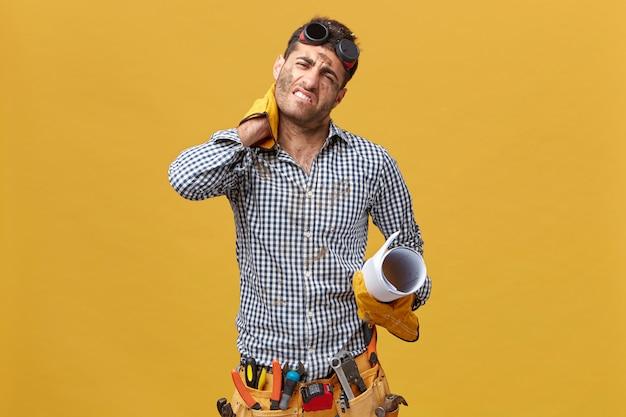Усталый ремонтник, измученный после долгого и напряженного рабочего дня, держит руку на шее и испытывает боль в перчатках, поясе с инструментами и перчатками и держит план изолированным