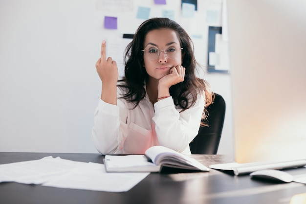 Tired and rude young woman employee showing middle finger to camera