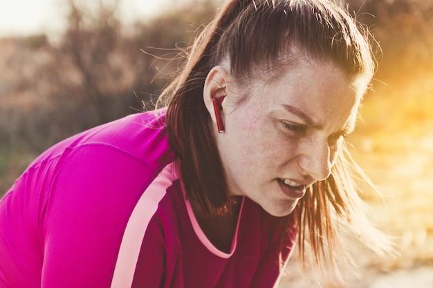 Уставшая бегунья чувствует себя плохо после пробежки или кардио тренировки на улице в солнечный день