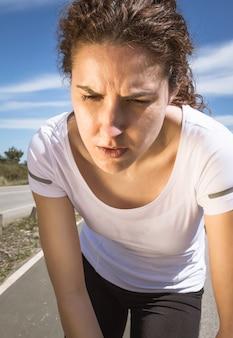 太陽と一緒に走った後に汗をかく疲れたランナーの女の子