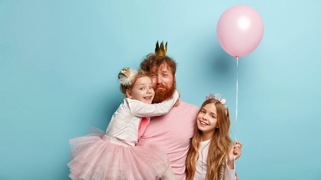 Tired sad single father organizes real holiday for children, wears crown, receives hug from small daughter, little girl with long hair holds air balloon, smiles happily stands near. family celebration