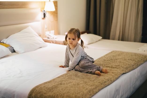 ベッドの上のホテルの部屋に座っている疲れた悲しい幼児の子供の女の子