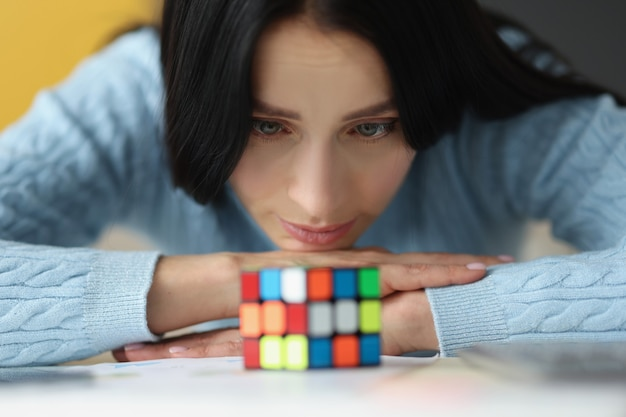 Tired sad woman looks at uncollected rubik cube making important decisions concept