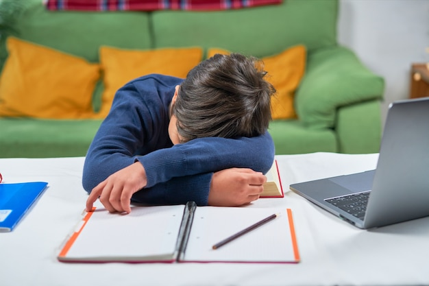 A tired school boy sleeping at desk while doing homework, home interior