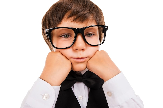 Tired schoolboy. bored little boy leaning his face on hands and looking at camera while isolated on white