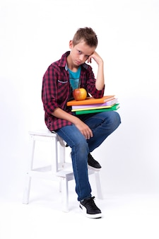 Tired schoolboy european appearance in shirt and jeans sitting