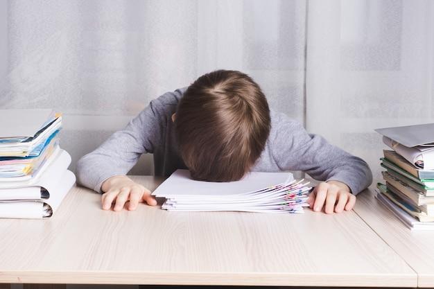 Усталый школьник лежит на столе, схватившись за голову от слишком много работы