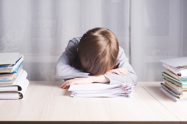 紙の上にテーブルの上に横たわって疲れた男子生徒