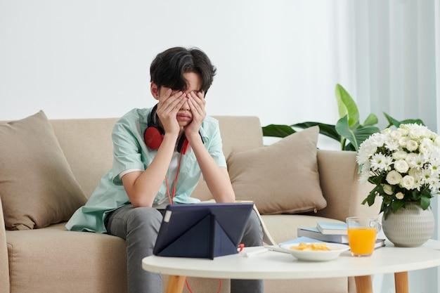 지친 남학생은 온라인 수업에 참석하고 집에서 여러 시간 동안 태블릿 컴퓨터로 교육 비디오를 본 후 눈을 비비고 있습니다.