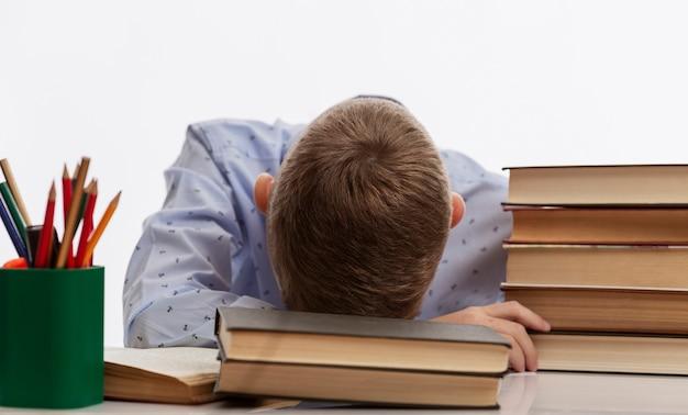 Уставший школьник сидит за столом и упирается головой в учебники.