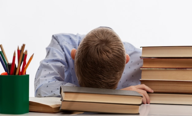 Tired schoolboy sits at a table and rested his head on textbooks.