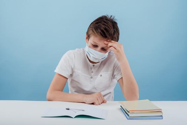 의료용 마스크를 쓴 지친 남학생은 파란색 배경에 격리된 테이블에 앉아 머리에 손을 얹고 있습니다...