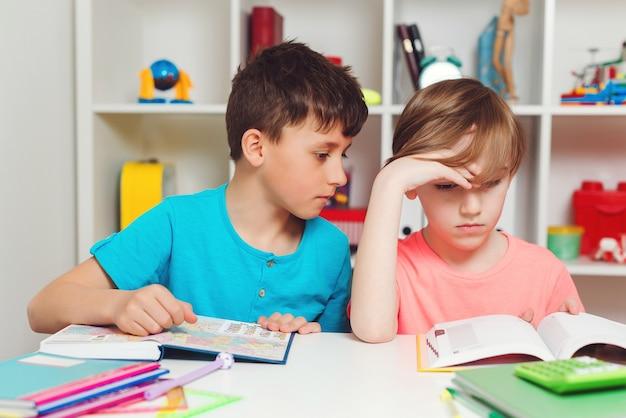 疲れた小学生は学校で本を読んでいます。レッスンを学ぶ悲しい男子生徒。