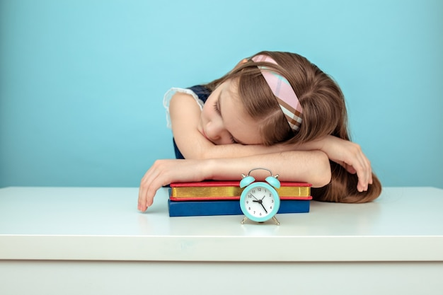 Tired schoolgirl sleeps over her books with next to a watch on light blue background.