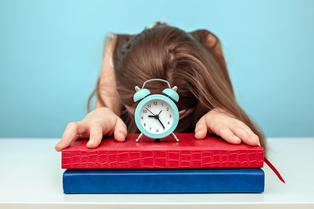 Tired schoolgirl sleeps over her books with a watch on them on light blue background.