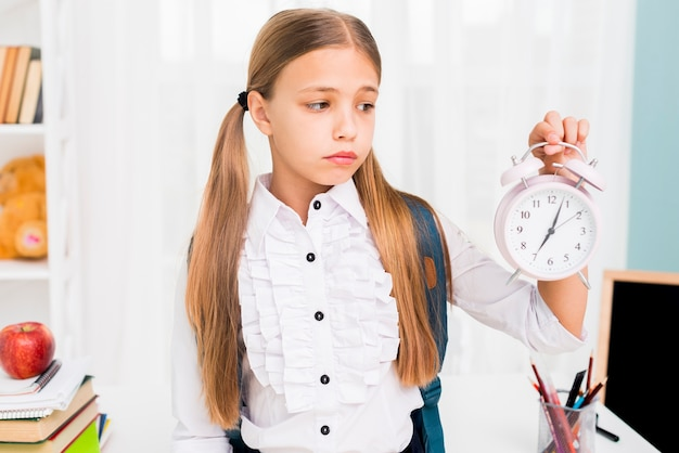 Tired schoolgirl with backpack holding clock in classroom