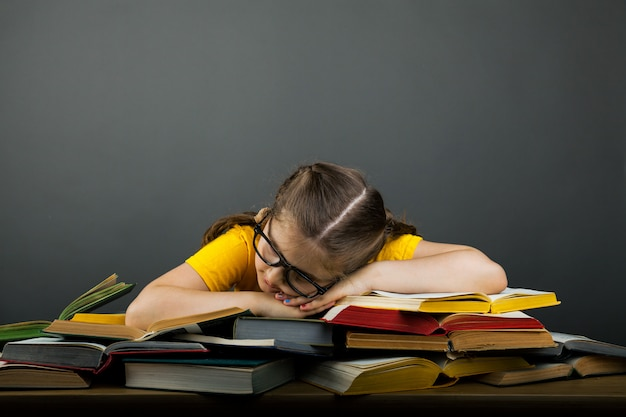 Tired schoolgrl with glasses sleeping on books in the library