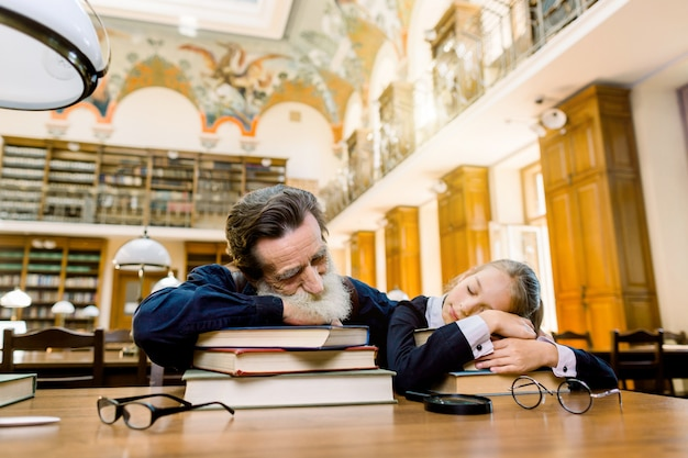 Tired senior bearded man teacher professor and his student or granddaughter are sleeping in a library liying on the table