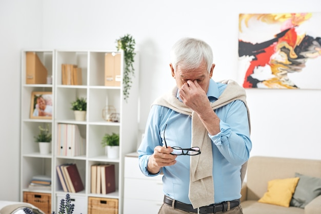 Tired senior man in blue shirt holding eyeglasses and rubbing bridge of nose while feeling eye fatigue at home