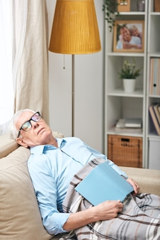 Tired senior man in glasses sitting under plaid on sofa and sleeping with book in living room