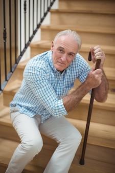 Tired senior man sitting on stairs