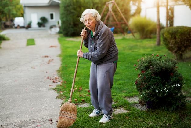 家の裏庭でほうきを持って疲れている年配の女性。