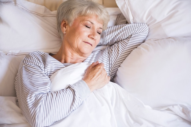 Tired senior woman sleeping in bed
