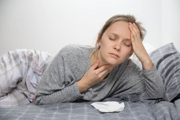 Tired sick woman in bed with closed eyes having sore throat